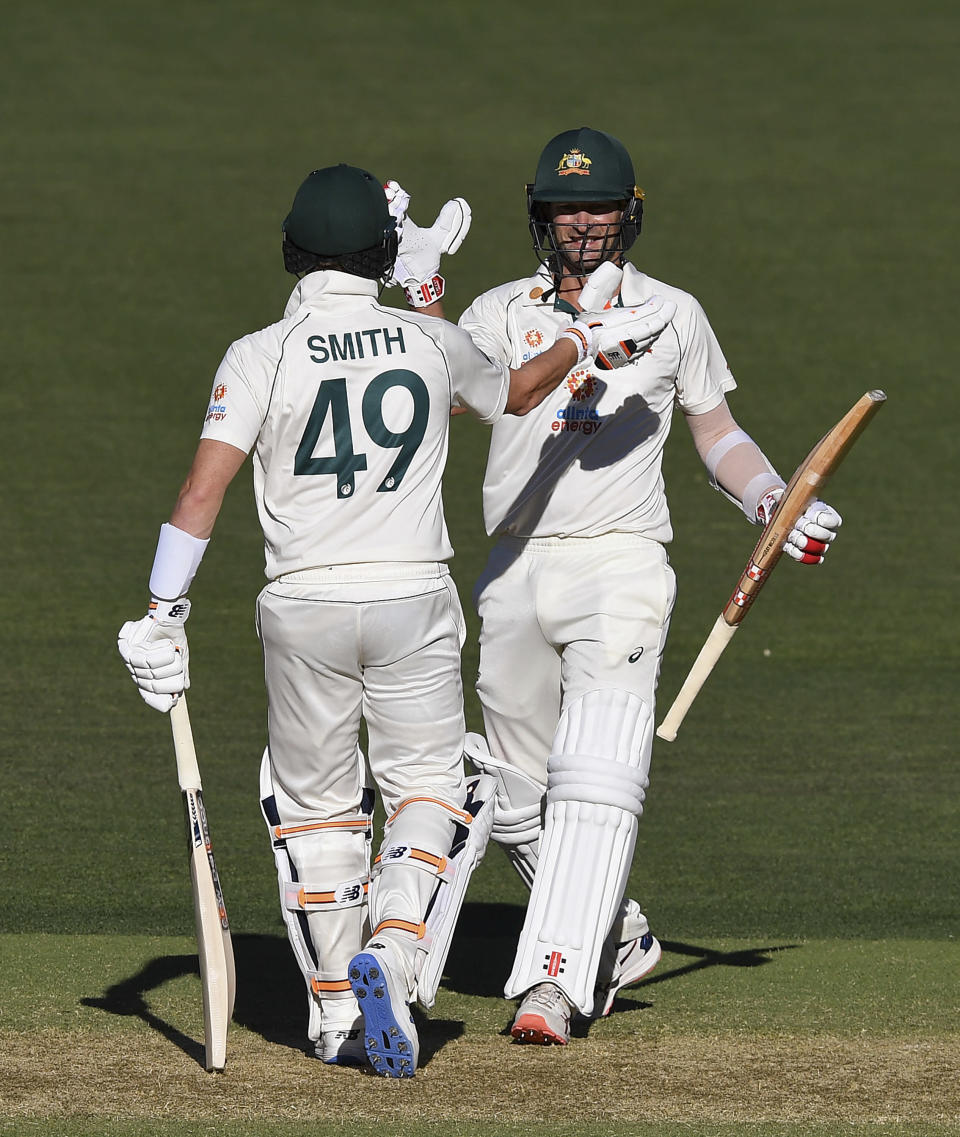 Australia's Joe Burns, right, is congratulated by teammate Steve Smith after hitting a 6 to win their cricket test match against India on the third day at the Adelaide Oval in Adelaide, Australia, Saturday, Dec. 19, 2020. (AP Photo/David Mariuz)