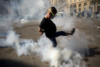 A man kicks away a tear gas canister during a yellow vest demonstration in Paris, Saturday, April 20, 2019. French yellow vest protesters are marching anew to remind the government that rebuilding the fire-ravaged Notre Dame Cathedral isn't the only problem the nation needs to solve. (AP Photo/Francisco Seco)
