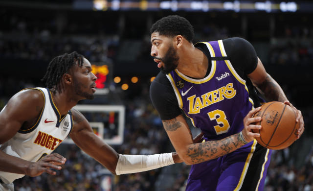 Los Angeles Lakers forward Anthony Davis, right, looks to pass the ball as Denver Nuggets forward Jerami Grant defends during the first half of an NBA basketball game Wednesday, Feb. 12, 2020, in Denver. (AP Photo/David Zalubowski)