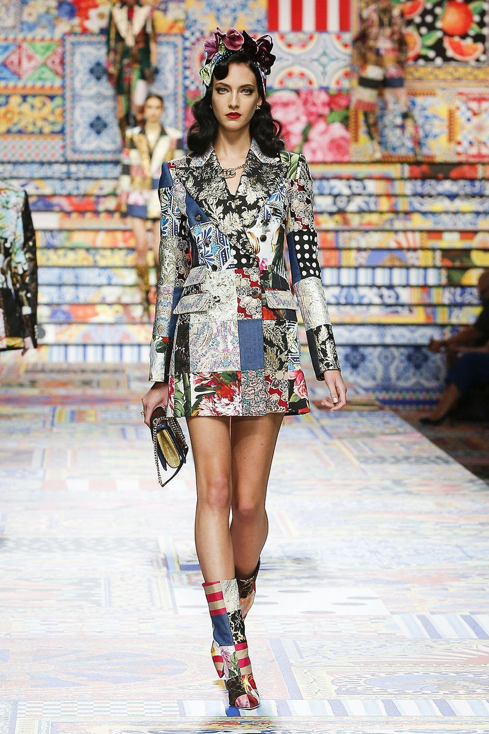 """<p>Spring 2021 will always be remembered as Dolce & Gabbana's """"patchwork collection,"""" an explanation-not-required moniker that future fashion historians can point to as an example of how designers adapted to circumstances beyond their control this season. The house was one of many who saw their access to fabrics affected by the pandemic, instead being forced to use bolts they might have had tucked away for a rainy day. In their case, what was available wasn't slim pickings, but luxe brocades, floral silks, and dotted chiffons. Intriguingly, the print combos both exaggerated and disguised different signature aspects of Dolce. The bold clashes furthered the over-the-top feeling they've made a calling card while simultaneously making it harder to spot their Italian bombshell. There were bustier dresses and thigh-high slits (of course), but they didn't whistle quite as loudly when tucked in amongst prints that positively shouted. <em>—Leah Melby Clinton</em></p>"""