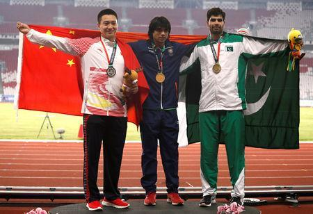 Athletics - 2018 Asian Games - Men's Javelin Throw - GBK Main Stadium, Jakarta, Indonesia - August 27, 2018 Gold medalist Neeraj Chopra of India on the podium with silver medalist Qizhen Liu of China (L) and bronze medalist Arshad Nadeem of Pakistan (R) REUTERS/Darren Whiteside