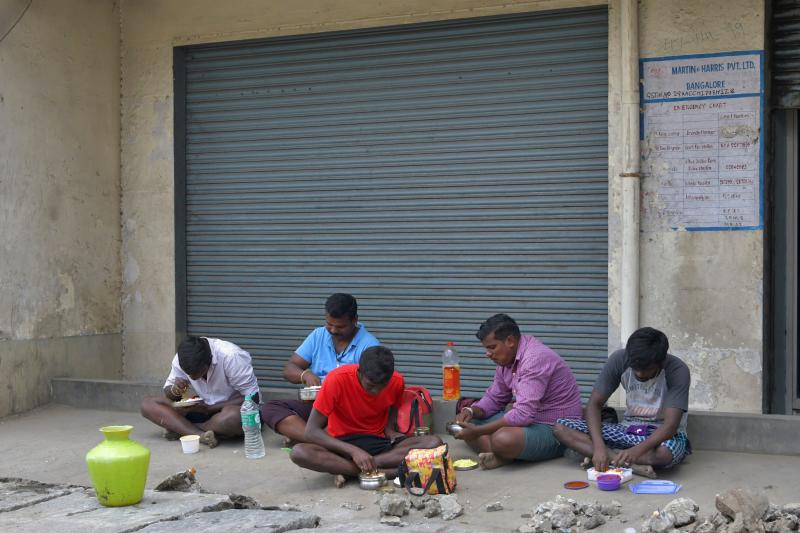 Labourers eat lunch in front of a closed retail shop in a street during a lockdown to contain the surge of COVID-19 coronavirus cases, in Bangalore on July 20, 2020. - India on July 17 hit a million coronavirus cases, the third-highest total in the world, with no sign yet of the infection curve flattening as new cases emerge in rural areas. More than 25,000 people have died nationally. (Photo by Manjunath Kiran / AFP) (Photo by MANJUNATH KIRAN/AFP via Getty Images)