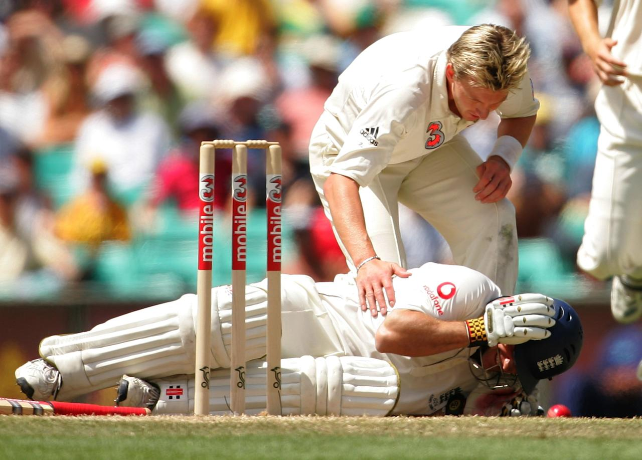 SYDNEY, AUSTRALIA - JANUARY 04:  Andrew Strauss (L) of England receives attention from Brett Lee of Australia after receiving a blow to the helmet from a Lee delivery during day three of the fifth Ashes Test Match between Australia and England at the Sydney Cricket Ground on January 4, 2007 in Sydney, Australia.  (Photo by Ezra Shaw/Getty Images)