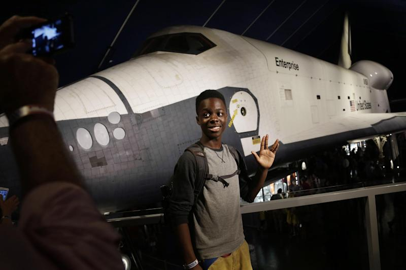 """Akil Grubb poses for a picture while flashing the hand signal made popular on """"Star Trek"""" in the newly completed pavilion that houses the space shuttle Enterprise on the deck of the Intrepid Sea, Air & Space Museum in New York, Wednesday, July 10, 2013. With a ribbon-cutting ceremony the pioneering shuttle has been restored from the damages it incurred during Superstorm Sandy. (AP Photo/Seth Wenig)"""
