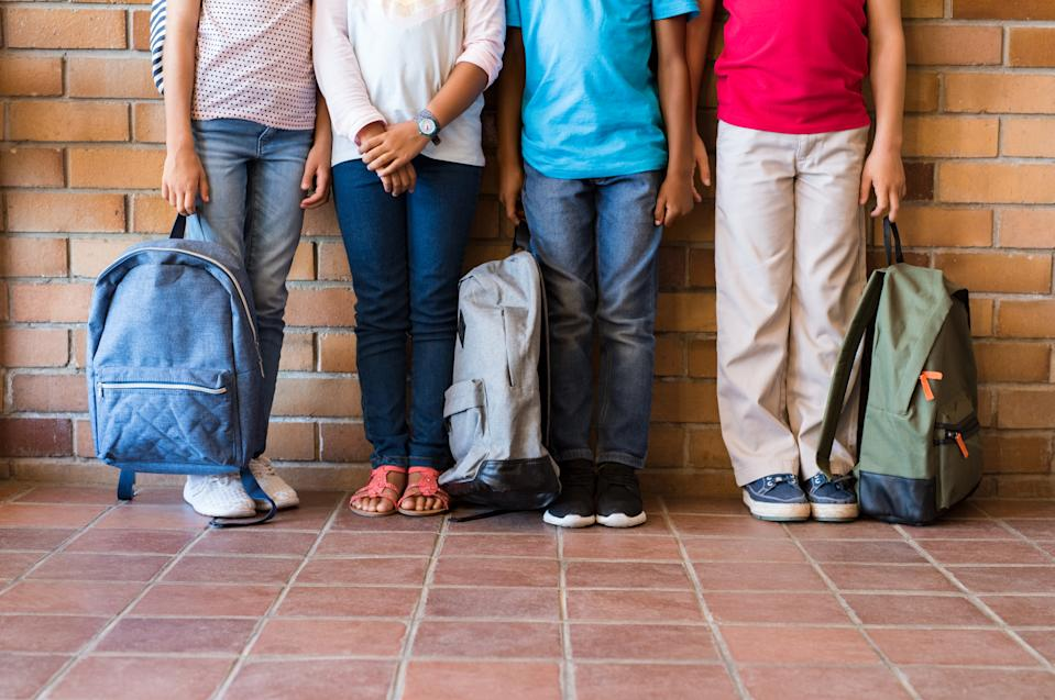 Low section of elementary students standing outside class with backpacks. Legs of four boys and girls leaning in a row. Four multiethnic school children before the start of the lessons.