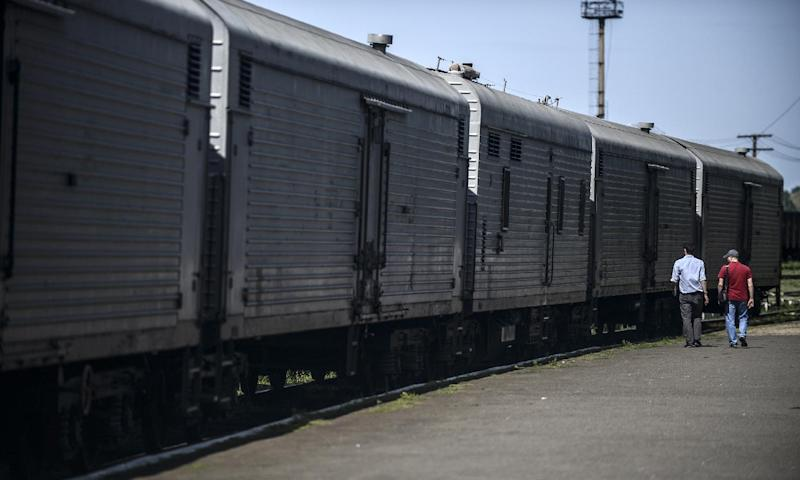 Journalists walk next to refrigerated wagons at a Ukrainian railway station in Torez, on July 20, 2014. Employees and residents said the wagons contain bodies of passengers of the Malaysia Airlines plane which crashed on July 17, 2014 (AFP Photo/Bulent Kilic)