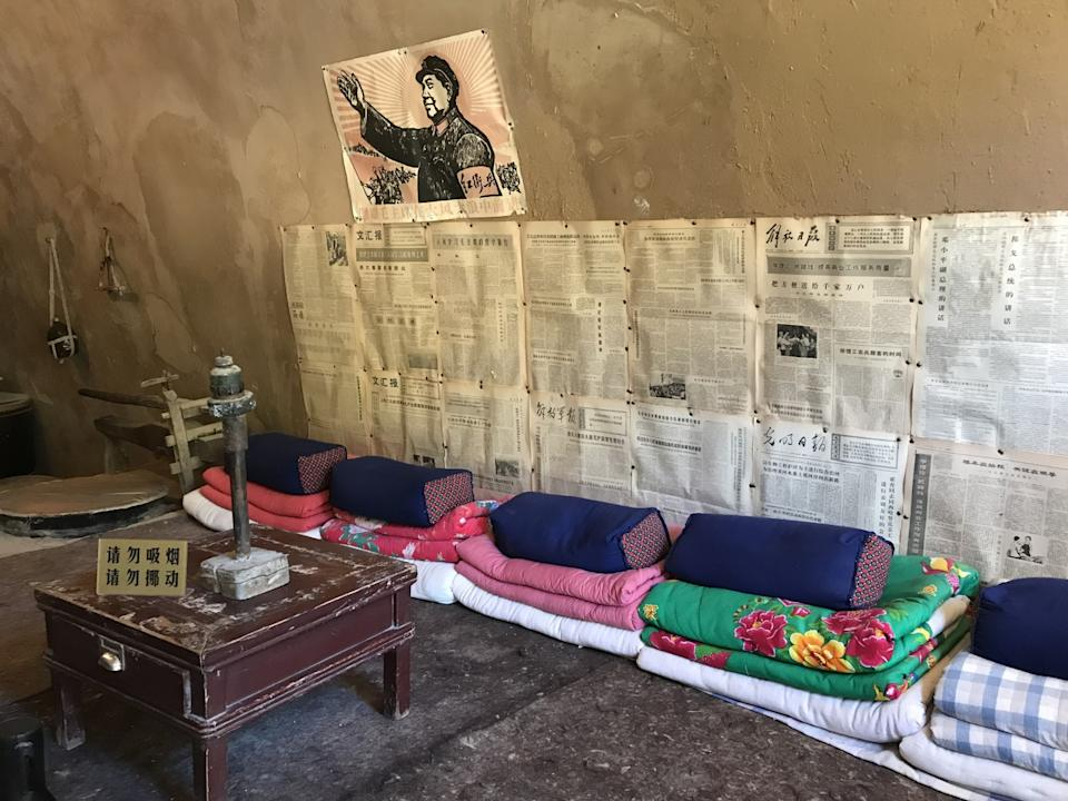 A poster of Mao and old newspapers hang on the wall in a cave.