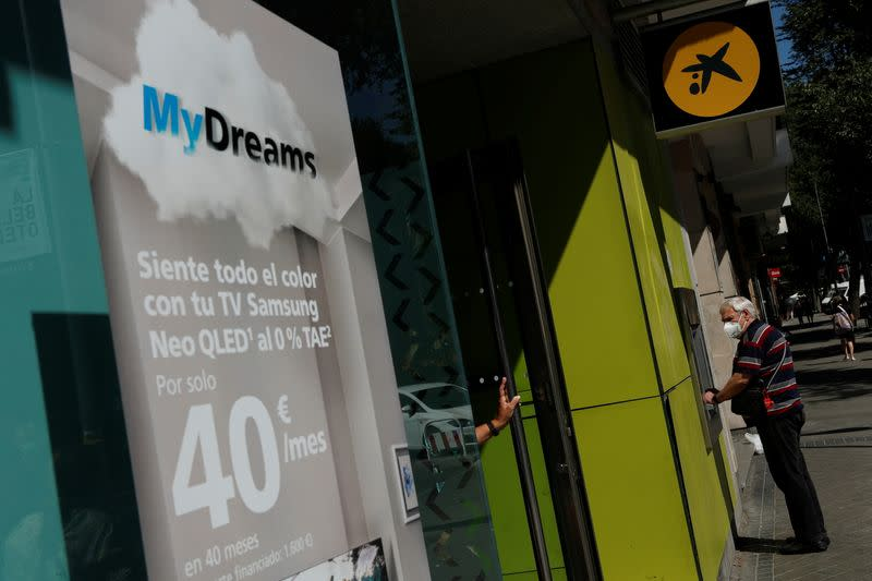 """A man uses an ATM machine next to a poster advertising Caixabank's consumer financing programme """"MyDreams"""" in Madrid"""