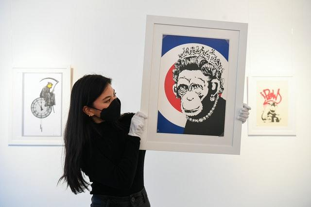 Gallery assistant Sophia Shim holds a limited edition print of Monkey Queen (2003) by Banksy