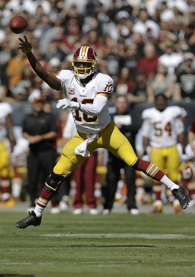 Washington Redskins quarterback Robert Griffin III (10) passes against the Oakland Raiders during the second quarter of an NFL football game in Oakland, Calif., Sunday, Sept. 29, 2013. (AP Photo/Marcio Jose Sanchez)