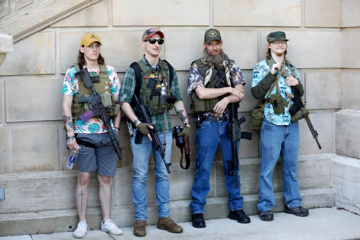 """Armed protesters take part in """"Operation Haircut,"""" organized by the Michigan Conservative Coalition in opposition to mandatory lockdown measures to curtail the coronavirus pandemic, outside the Michigan State Capitol in Lansing, Mich. on May 20, 2020. The Hawaiian shirts are a kind of uniform for members of the extremist boogaloo movement.  (Jeff Kowalsky/AFP via Getty Images)"""