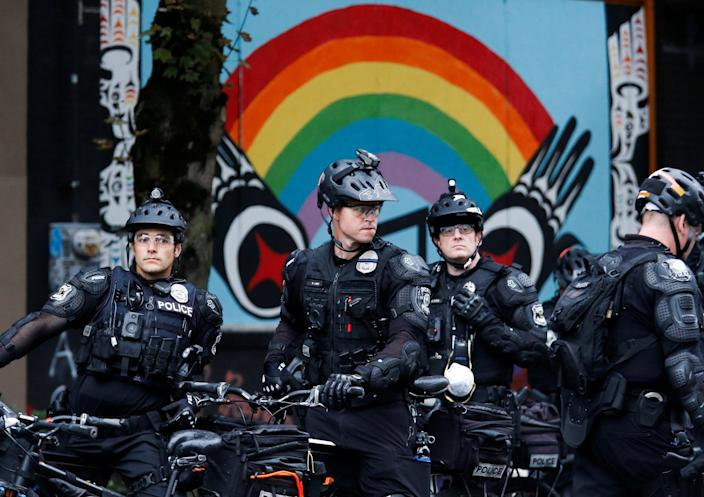 Officers on bicycles stand under a rainbow mural as Seattle Police retake the Capitol Hill Occupied Protest (CHOP) area, including their East Precinct, in Seattle, Washington (REUTERS)