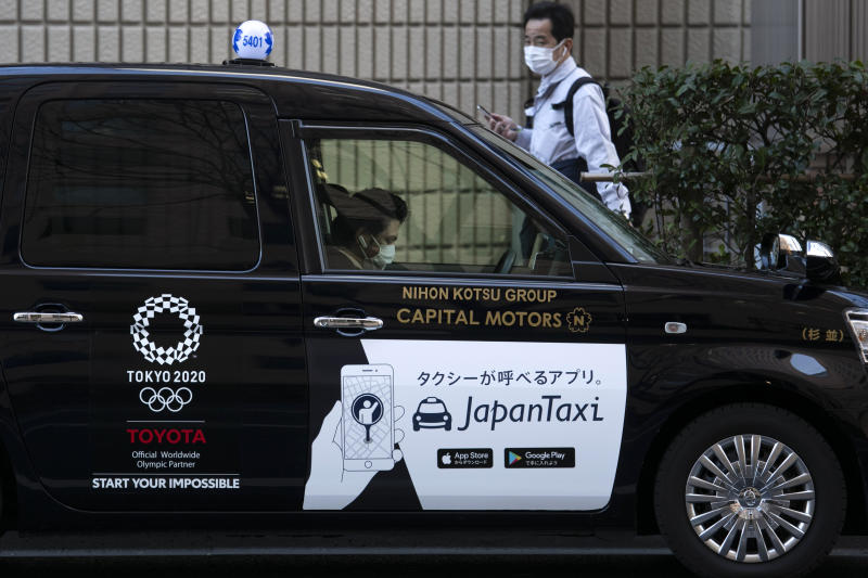 FILE - In this Tuesday, Feb. 18, 2020, file photo, a taxi driver wearing a mask waits for a fare with a Tokyo 2020 logo on the door of his car in Tokyo. The Tokyo Olympics open in exactly five months on July 24. But the fast-spreading coronavirus from China is making Tokyo organizers very anxious. Three deaths have been reported in Japan with more than 700 cases, more than 600 from a cruise ship that docked in Japan. (AP Photo/Jae C. Hong, File)