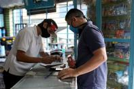 Physical education teacher Victor Carrillo buys supplies at a shop in Caracas