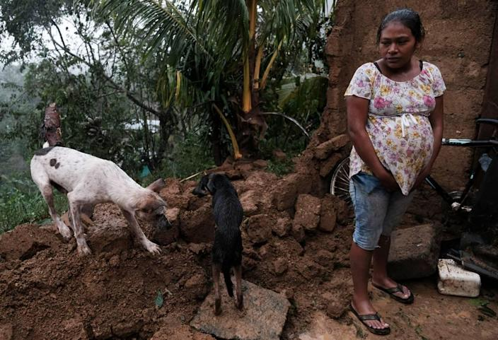 A woman stands by the fallen wall of her house after the passage of Hurricane Iota in Siuna, Nicaragua, Tuesday, Nov. 17, 2020.