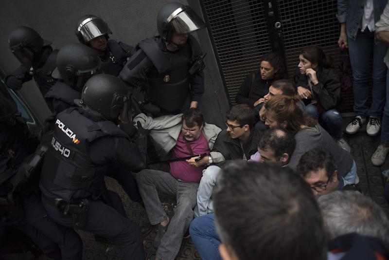 Riot police clash with members of the public outside a school being used as a polling station for the banned referendum.