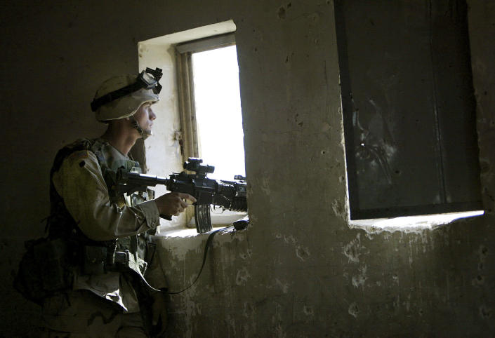 FILE - In this April 29, 2003, file photo, U.S. soldier mans a position from a primary school window in Fallujah, Iraq. The U.S. launched its invasion of Iraq on March 20, 2003, unleashing a war that led to an insurgency, sectarian violence and tens of thousands of deaths. (AP Photo/David Guttenfelder, File)