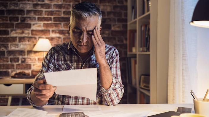 Worried mature man checking his domestic bills at home, he is concerned and reading his financial statements.