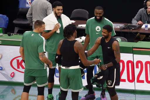 Brooklyn Nets guard Kyrie Irving, right, smiles as he exchanges jerseys with former Boston Celtics teammate center Robert Williams III after an NBA preseason basketball game, Friday, Dec. 18, 2020, in Boston. (AP Photo/Mary Schwalm)