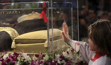 An altar boy touches the glass where the exhumed body of the mystic saint Padre Pio lies in the Catholic church of San Lorenzo fuori le Mura in Rome, February 3, 2016. REUTERS/Yara Nardi