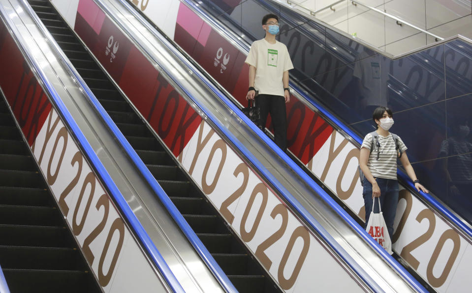 In this July 7, 2021, file photo, people wearing face masks ride an escalator with banners to promote the Tokyo Olympics scheduled to open on July 23, in Tokyo. The pandemic-delayed Tokyo Olympics are shaping up as a TV-only event with few fans — if any — being allowed when they open in just over two weeks. Japan's Asahi newspaper, citing multiple unidentified government sources, says the opening ceremony will be limited only to VIP guests. (AP Photo/Koji Sasahara, File)