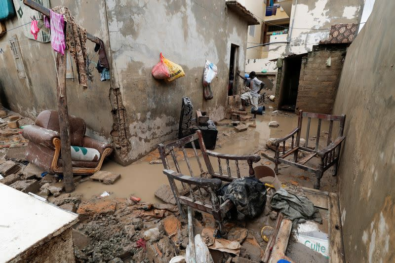 A man stands at a house's flooded courtyard after heavy rains in the Ndiaga Mbaye district on the outskirts of Dakar