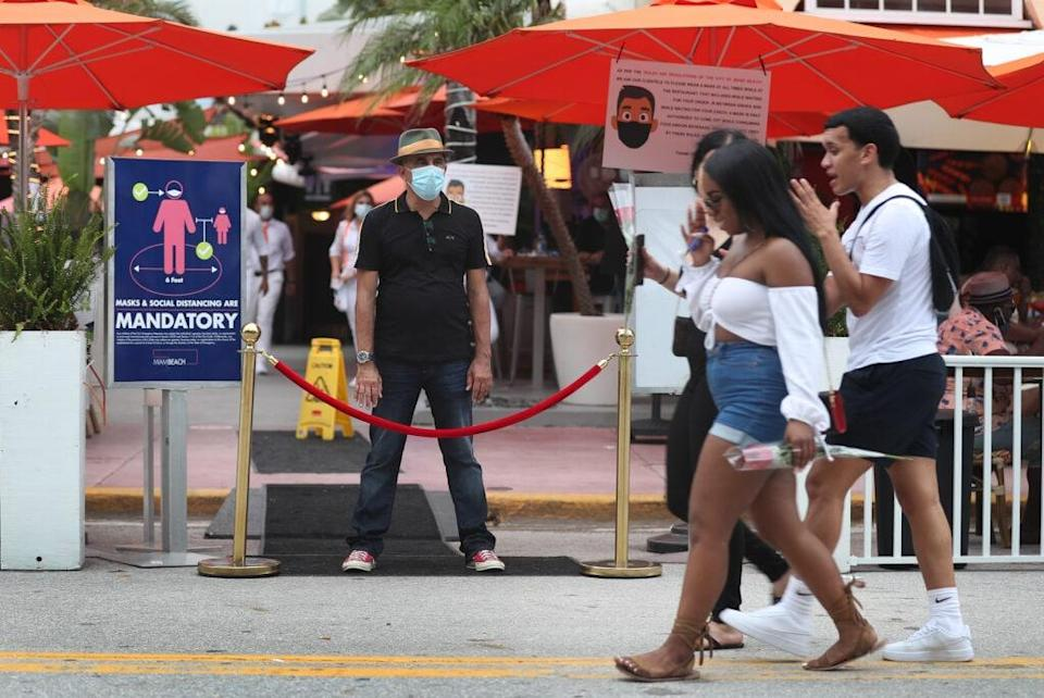 Juan Carlos, a host at Ocean 10 restaurant, stands at the entrance of the restaurant to turn customers away as a curfew from 8pm to 6am is put in place on July 18, 2020 in Miami Beach, Florida. (Photo by Joe Raedle/Getty Images)