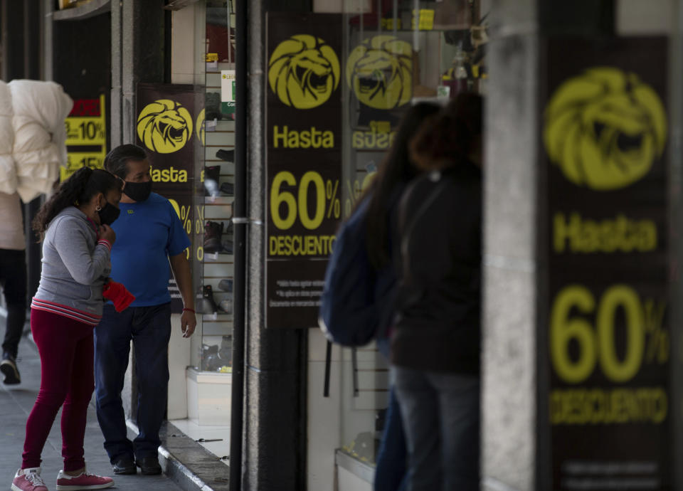 Shoppers look into a store announcing discounts in downtown Mexico City, Friday, Oct. 30, 2020. Prior to the coronavirus pandemic, Mexico's economy was in recession, and that only deepened with the economic shutdown provoked by measures aimed at slowing the spread of COVID-19 during the second quarter. (AP Photo/Fernando Llano)