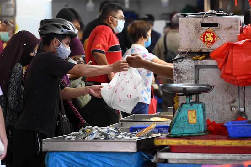 A man, wearing a face mask as a preventive measure against the spread of the COVID-19 novel coronavirus, makes a purchase at a fish stall in Geylang Serai wet market in Singapore on April 23, 2020, ahead of the start of the holy Muslim month of Ramadan. (Photo by Roslan RAHMAN / AFP) (Photo by ROSLAN RAHMAN/AFP via Getty Images)