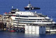 "The cruise liner Costa Concordia is seen at Giglio harbour, Giglio Island July 13, 2014. Italian authorities gave the green light to refloating the wrecked Costa Concordia cruise ship on Saturday, setting the stage for the next step in the largest maritime salvage in history to begin on Monday morning. The defunct luxury liner is due to depart Giglio on July 21, two and a half years after it struck a reef while performing a display manoeuvre to move close to shore and ""salute"" the port. REUTERS/Alessandro Bianchi (ITALY - Tags: DISASTER TRANSPORT MARITIME)"