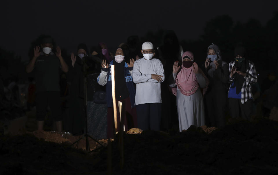 Family members pray during a burial of their relative at the special section of the Pedurenan cemetery designated to accommodate the surge in deaths during the coronavirus outbreak in Bekasi, West Java, Indonesia, Friday, July 30, 2021.(AP Photo/Achmad Ibrahim)
