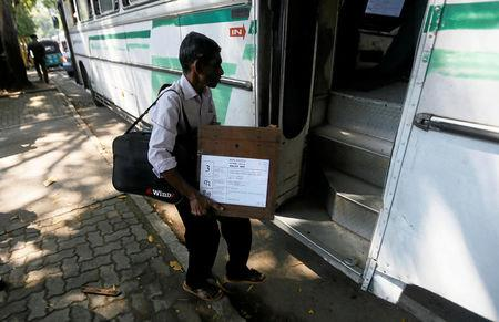 An electoral officials carries a ballot box as he waits get into a bus ahead of local government polls in Colombo, Sri Lanka February 9, 2018. REUTERS/Dinuka Liyanawatte