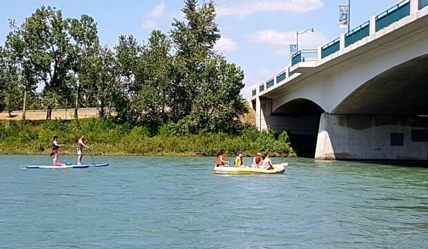 Rafters and paddleboarders make their way down the Bow River in Calgary on a sunny Monday afternoon. (Robson Fletcher/CBC - image credit)