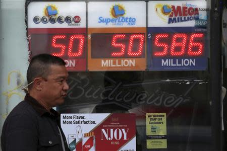 A man walks past a Mega Millions lottery sign with the estimated jackpot of $586 million posted in Alhambra, California December 16, 2013. REUTERS/Jonathan Alcorn