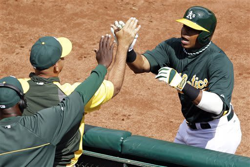 Oakland Athletics designated hitter Yoenis Cespedes, right, is greeted near the dugout after hitting a three-run home run off San Francisco Giants starting pitcher Ryan Vogelsong during the third inning of their exhibition baseball game, Saturday, March 30, 2013, in Oakland, Calif. (AP Photo/Eric Risberg)