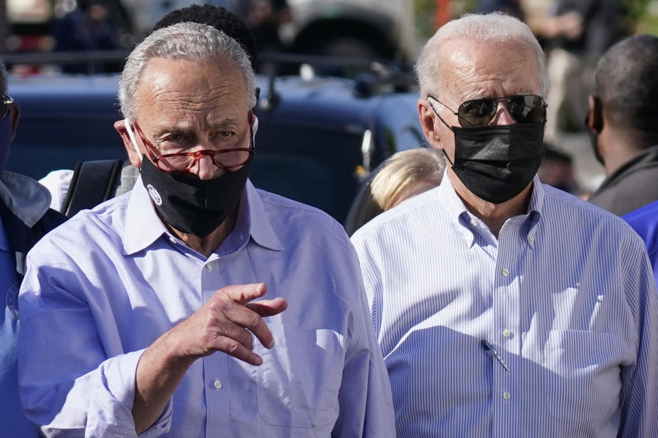 President Joe Biden tours a neighborhood impacted by flooding from the remnants of Hurricane Ida, Tuesday, Sept. 7, 2021, in the Queens borough of New York, with Senate Majority Leader Chuck Schumer of N.Y. (AP Photo/Evan Vucci)