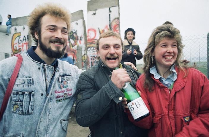 Bernd Mechelke of Ingolstadt, West Germany, welcomes his friends from Woltersdorf, East Germany, with a bottle of champagne as they arrive in West Berlin on Nov. 12, 1989.