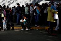 A man carrying a baby rests on the sidewalk as he queues to try and buy diapers outside a pharmacy in Caracas, Venezuela March 18, 2017. REUTERS/Carlos Garcia Rawlins