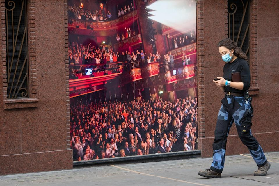 <p>A woman wearing a face mask passes a photo of a packed theatre auditorium in Soho</p> (PA)