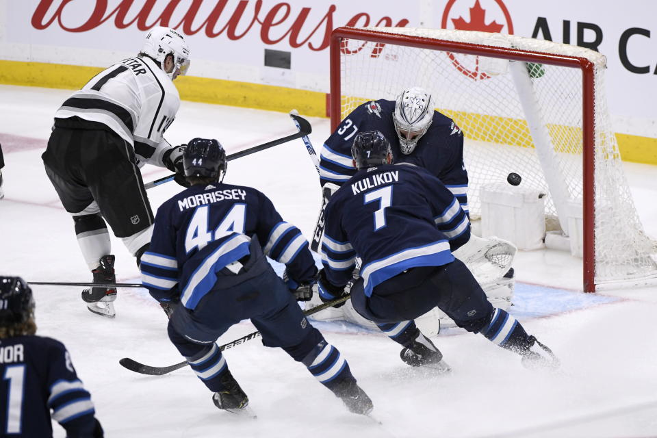 Los Angeles Kings' Anze Kopitar (11) scores against Winnipeg Jets goaltender Connor Hellebuyck (37) as Josh Morrissey (44) and Dmitry Kulikov (7) rush back to defend during the third period of an NHL hockey game Tuesday, Oct. 22, 2019, in Winnipeg, Manitoba. (Fred Greenslade/The Canadian Press via AP)