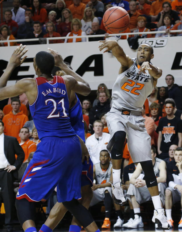 Oklahoma State wing Markel Brown (22) passes over Kansas center Joel Embiid (21) during the second half of an NCAA college basketball game in Stillwater, Okla., Saturday, March 1, 2014. Oklahoma State won 72-65. (AP Photo/Sue Ogrocki)