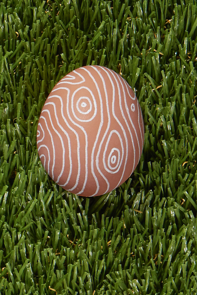 <p><em>Faux bois</em>, meaning false wood, refers to practice of imitating the look of wood grain on any other form of media. Use a white paint pen to draw irregular lines and concentric circles on your egg to get the look. (And hey, even if it's not convincing as<em> faux bois</em>, you'll probably still get a cool graphic design.)</p>