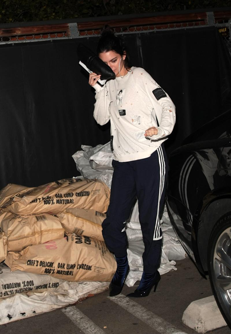 "For a night out in Los Angeles earlier this month, Kendall Jenner donned sweatpants with what Vogue calls ""<a href=""http://www.vogue.com/article/kendall-jenner-kim-kardashian-west-adidas-heels-celebrity-street-style"" target=""_blank"">patent and velvet stiletto boots</a>.""  (Splash News)"
