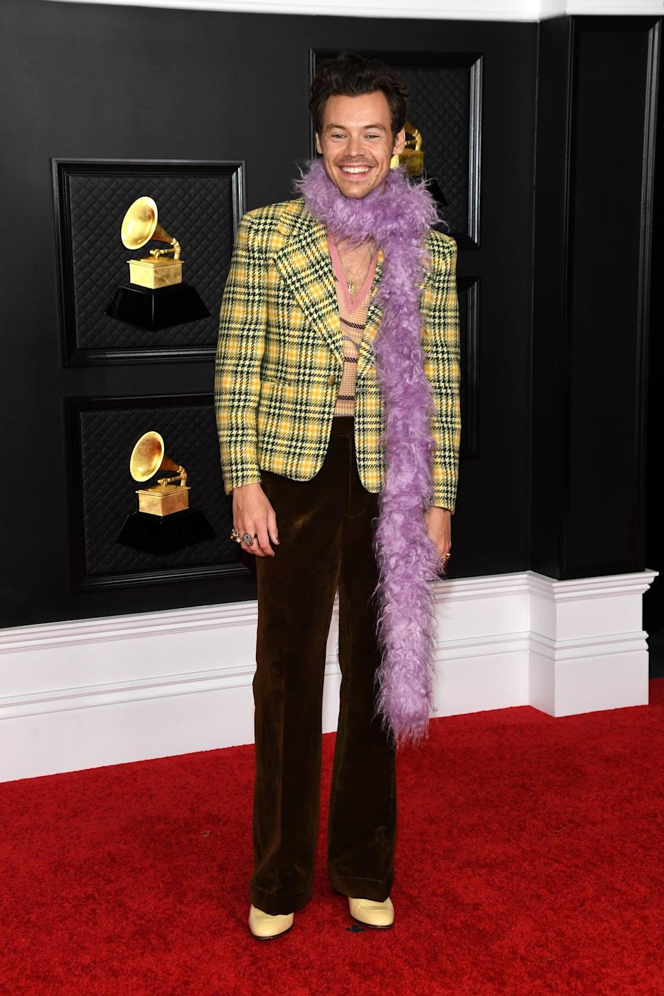 """<p>Psh, you didn't think we'd leave out this Gucci look, now did you? After lighting up the 2021 Grammys stage in <a href=""""https://www.popsugar.com/fashion/harry-styles-grammys-performance-outfit-2021-pictures-48216019"""" class=""""link rapid-noclick-resp"""" rel=""""nofollow noopener"""" target=""""_blank"""" data-ylk=""""slk:an all-leather ensemble"""">an all-leather ensemble</a>, Harry changed into this chic Cher Horowitz-inspired look consisting of a yellow houndstooth blazer, brown velvet pants, a purple fuzzy boa, and a pink plaid sweater vest with a deep-V neckline. Oh, and let's not forget about <a href=""""https://www.popsugar.com/fashion/harry-styles-banana-necklace-2021-grammys-48217742/"""" class=""""link rapid-noclick-resp"""" rel=""""nofollow noopener"""" target=""""_blank"""" data-ylk=""""slk:that risqué banana necklace of his"""">that risqué banana necklace of his</a> either.</p>"""