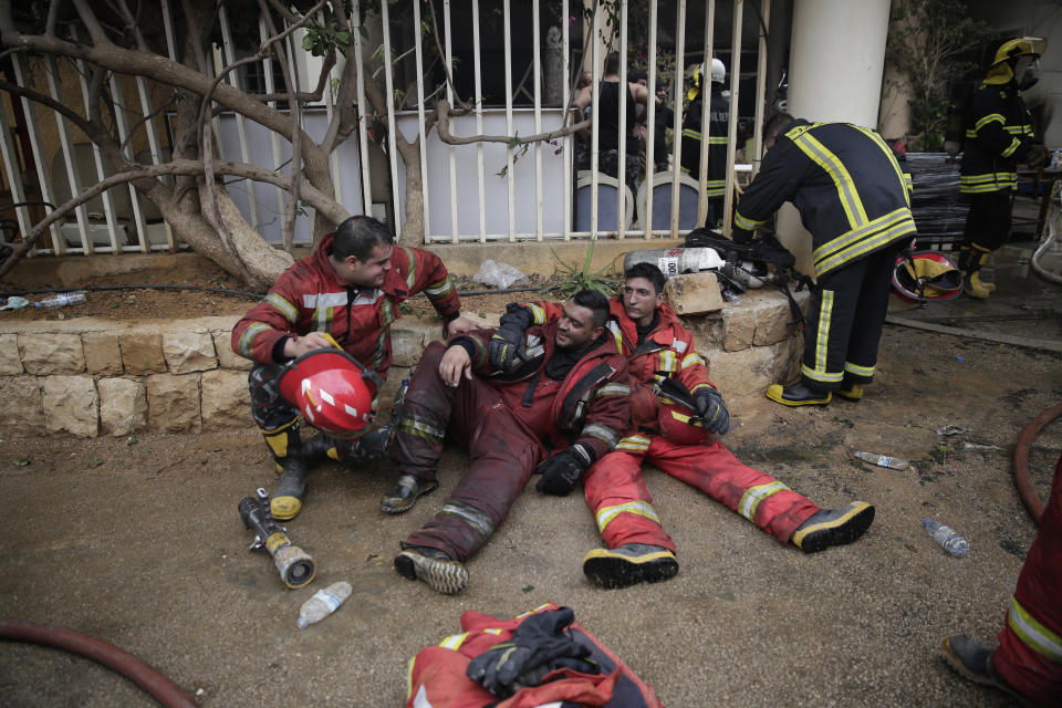 Lebanese firemen rest outside a building that was burned in a wildfire overnight, in the town of Damour, just over 15km (9 miles) south of Beirut, Lebanon, Tuesday, Oct. 15, 2019. Strong fires spread in different parts of Lebanon forcing some residents to flee their homes in the middle of the night as the flames reached residential areas in villages south of Beirut. (AP Photo/Hassan Ammar)