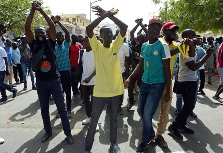 Demonstrators gesture during a protest in Dakar