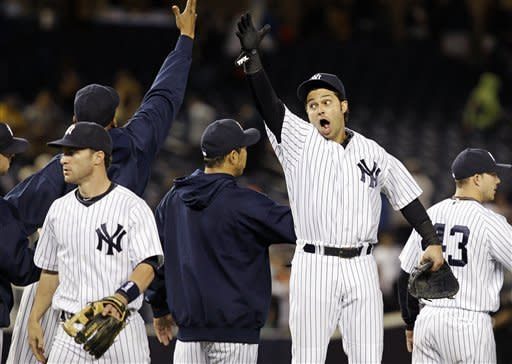 New York Yankees right fielder Nick Swisher, center, celebrates with teammates after their 10-7 win over the Toronto Blue Jays in their baseball game at Yankee Stadium in New York, Thursday, Sept. 20, 2012. (AP Photo/Kathy Willens)