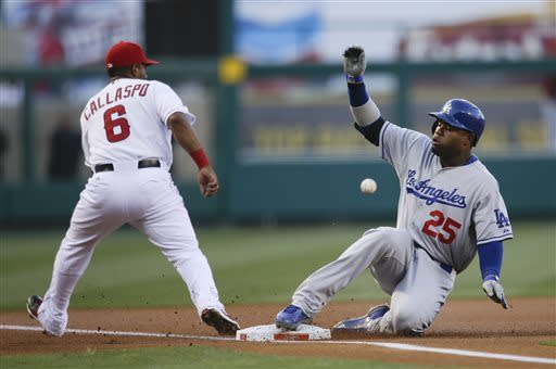 Los Angeles Dodgers' Carl Crawford, right, slides into third base as Los Angeles Angels third baseman Alberto Callaspo waits for the throw during the first inning of an interleague baseball game in Anaheim, Calif., Thursday, May 30, 2013. (AP Photo/Jae C. Hong)