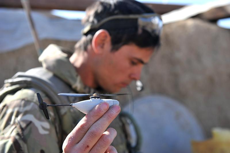 Undated image released by the British Army Monday Feb 4 2013 of Sergeant Scott Weaver, of The Queens Royal Lancers launching a newly issued Black Hornet miniature surveillance helicopter during an operation in Afghanistan. The Scandinavian-designed Black Hornet Nano weighs as little as 16 grams (0.56 ounces) — the same as a finch. The four-inch-long (10-centimeter-long) helicopter is fitted with a tiny camera which relays still images and video to a remote terminal. Troops used the drone to look for insurgent firing points and check out exposed areas of the ground before crossing. (AP Photo/ Sgt Ruper Frere)