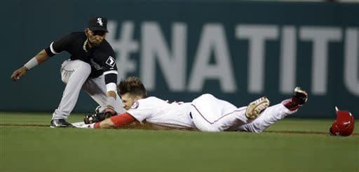 Washington Nationals' Bryce Harper is tagged out at second base by Chicago White Sox shortstop Alexei Ramirez, when Harper tried to squeeze his hit into a double, during the first inning of an interleague baseball game at Nationals Park Tuesday, April 9, 2013, in Washington. (AP Photo/Alex Brandon)